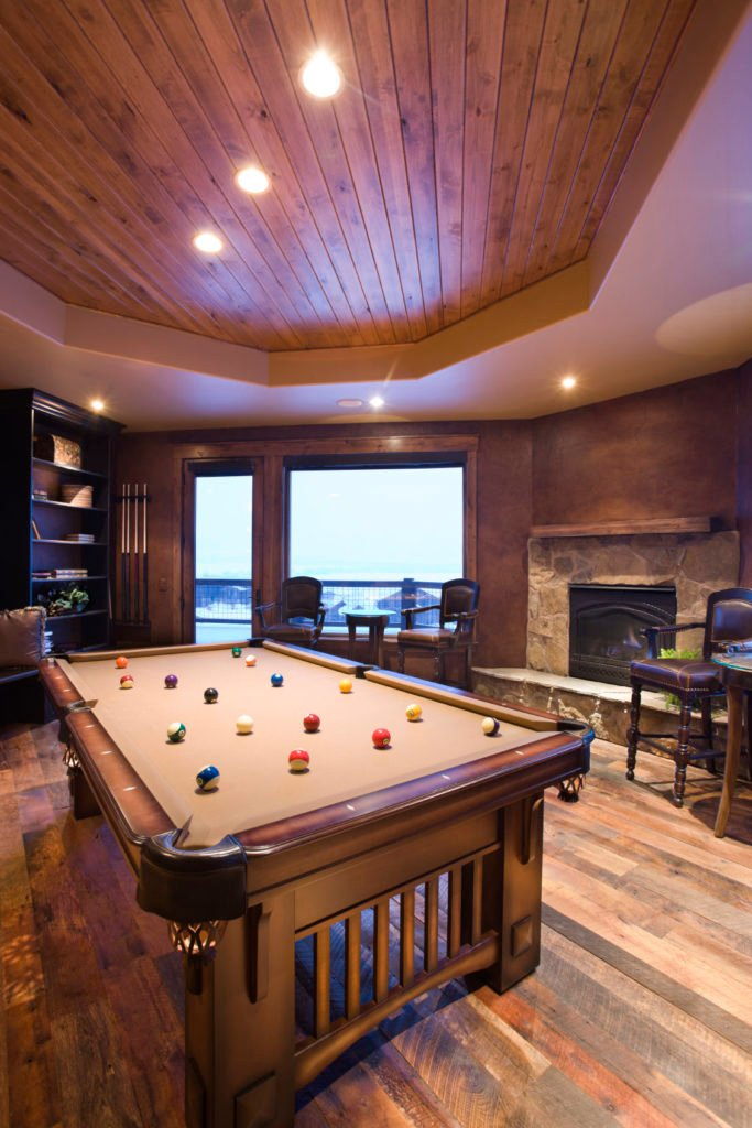 This game room features a stylish billiards pool set on the hardwood flooring and is lighted by recessed lights set on the tray ceiling.