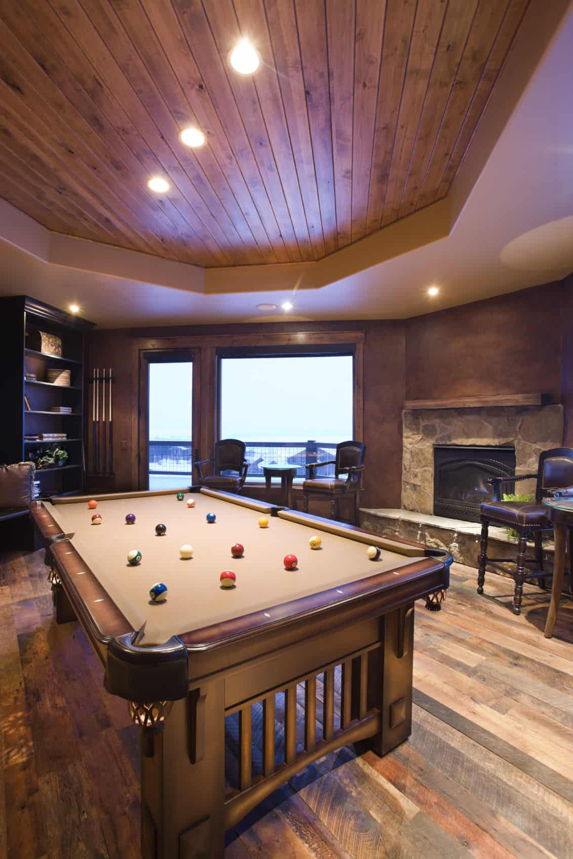 A beautiful man cave featuring hardwood flooring and a classy ceiling along with a stylish billiards pool.