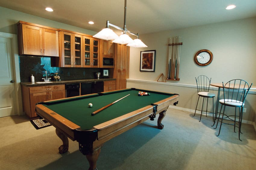 This game room boasts a classic billiards pool set on the carpet flooring lighted by a charming pendant lighting.