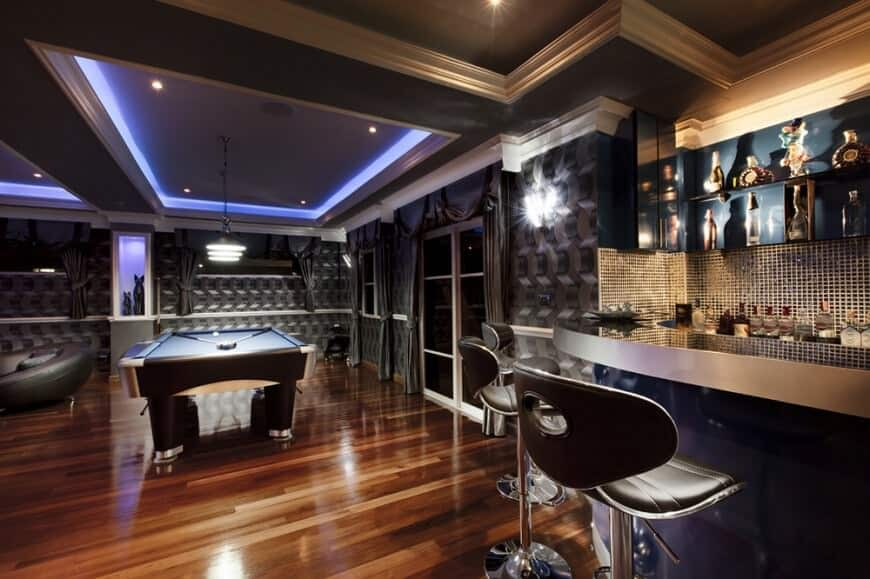 Modern home bars with hardwood flooring and multiple tray ceiling along with stylish designed walls.