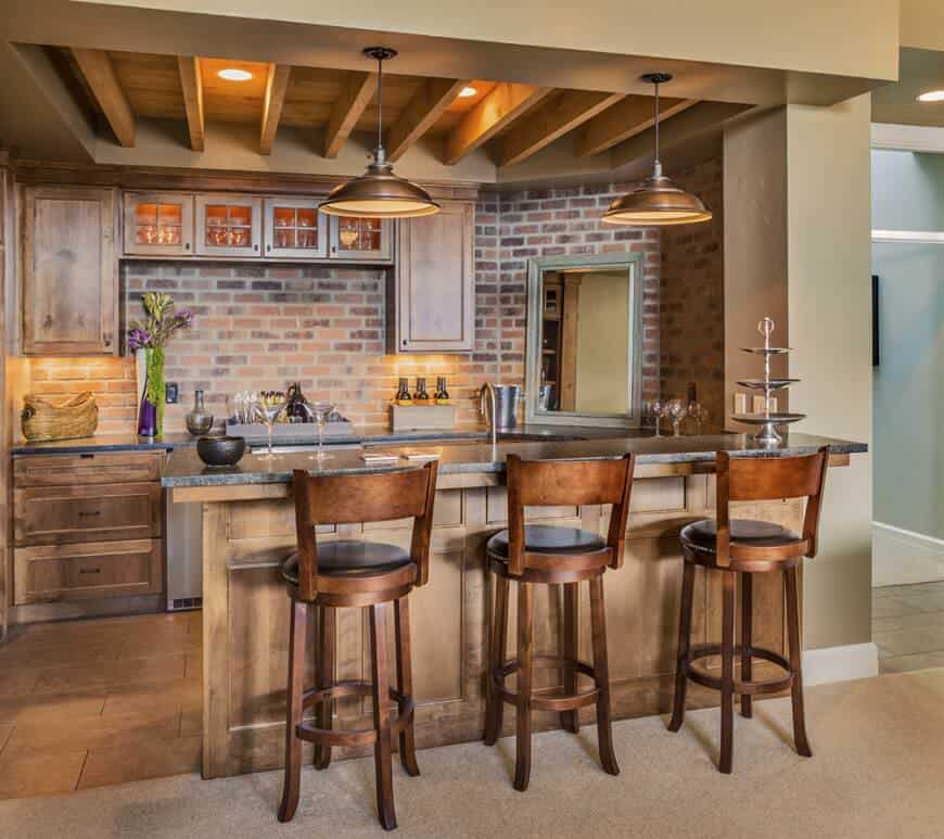 A contemporary home bar with brick walls and beams ceiling together with pendant and recessed ceiling lights.