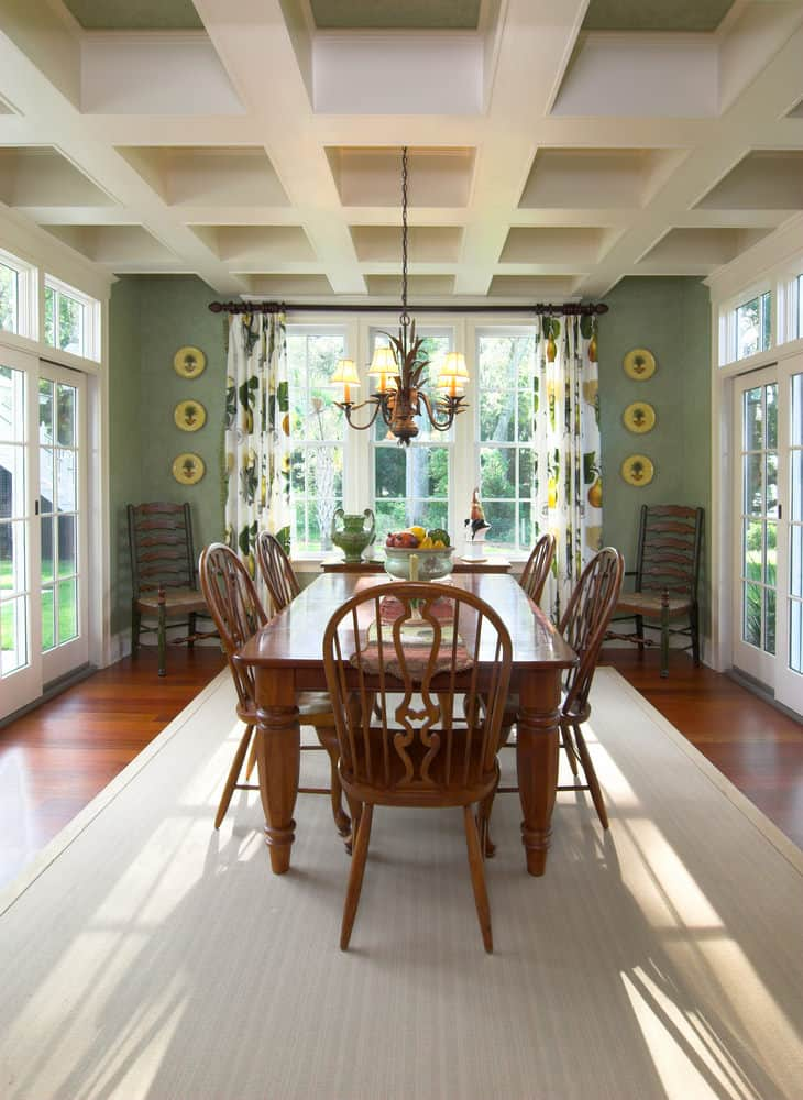 A classy dining room featuring green walls and hardwood flooring topped by a rug matching the white coffered ceiling.