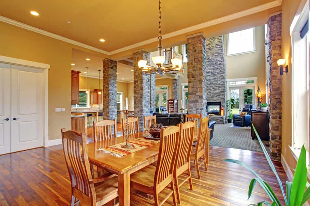 Warm dining room framed with stone brick columns that are fixed to the rich hardwood flooring and mustard ceiling. It includes a wooden dining set lighted by a wrought iron chandelier and matching wall sconce.