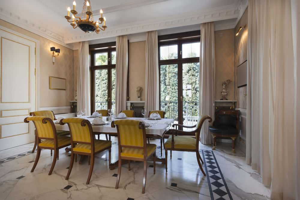 Cream dining area accented with yellow striped chairs that surround a rectangular dining table. It has full height glazing that allows natural light in.
