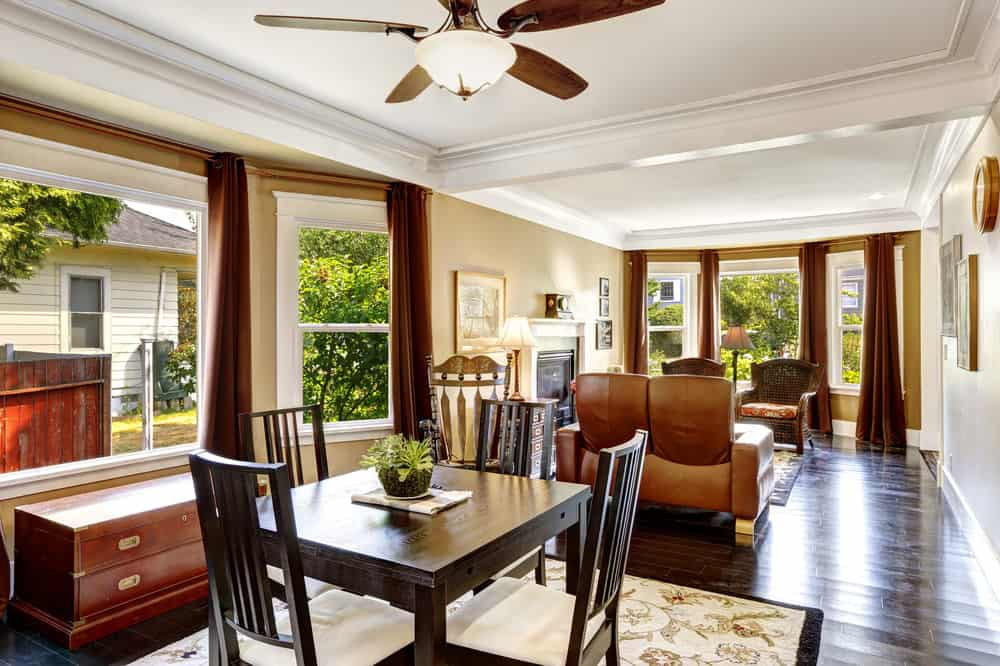 This home features an open space featuring a formal living room and square dining nook set on the hardwood flooring topped by classy rugs and are both under the home's tray ceiling.