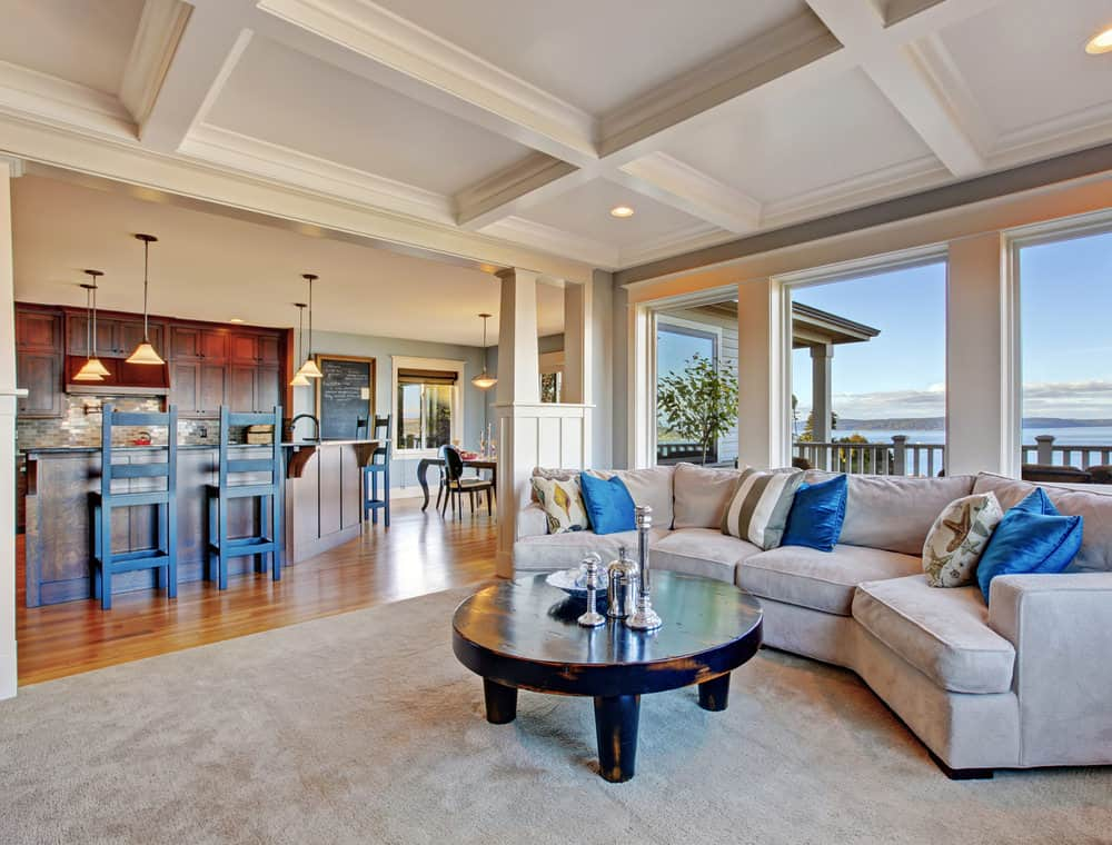 Large formal living space with a stylish sofa set matching the gray rug covering the hardwood flooring. The area also has a coffered ceiling.