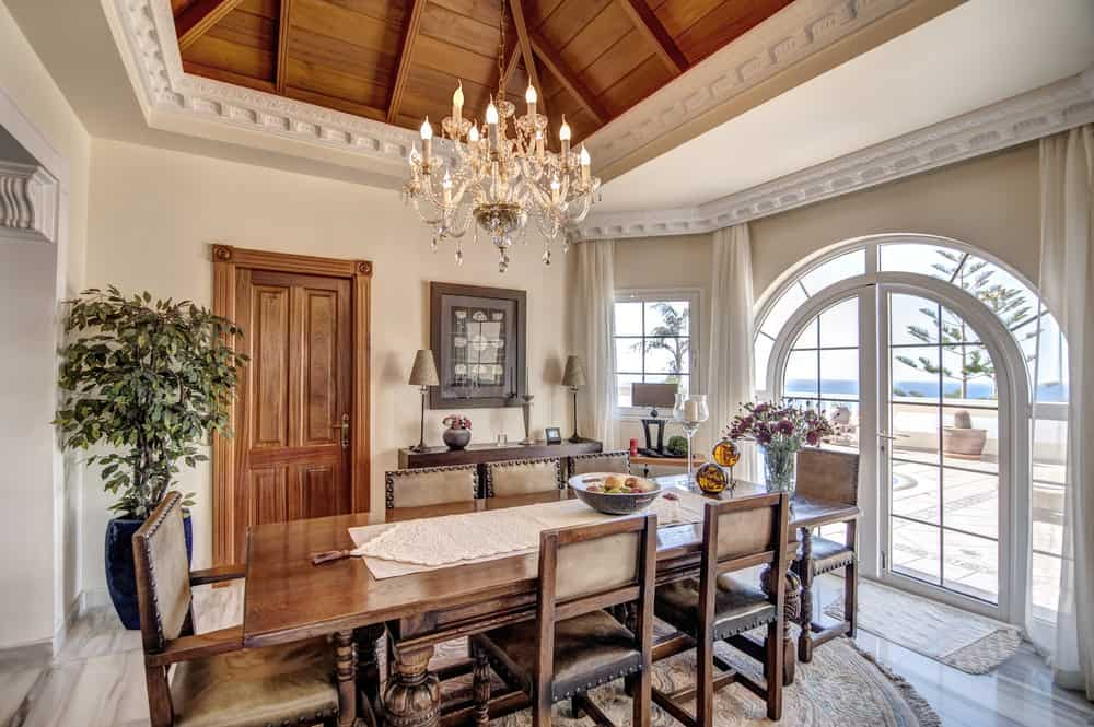 Fresh and airy dining room with wooden dining table paired with cushioned chairs. It features an arched paneled door covered with sheer curtains leading to an open balcony.