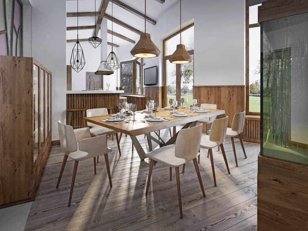 This dining room features a wooden dining table and chairs over light wood plank flooring illuminated by a pair of wooden pendant lights that hung from a vaulted ceiling lined with wood beams.