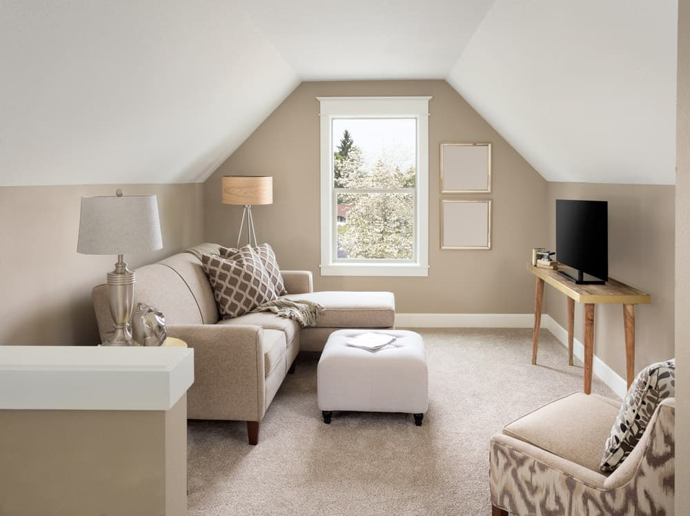 Small living room with beige walls and carpet flooring along with comfortable and classy seats.