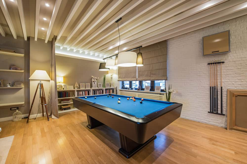 The billiards pool of this game room sure is stylish. The hardwood flooring and gray walls look perfect together with the classy pendant lights set on the stunning ceiling.