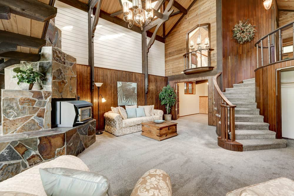 A stunning home setup with a living space with carpet floors and tall ceiling with exposed beams.