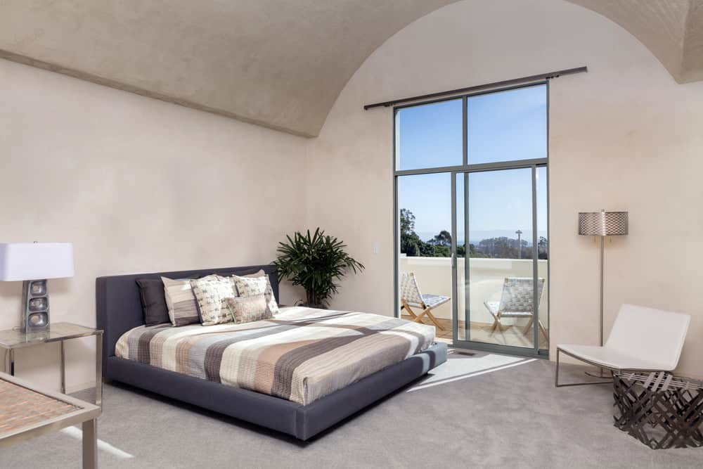 Spacious beige primary bedroom with barrel ceiling, carpet flooring, and sliding glass doors leading to the balcony.