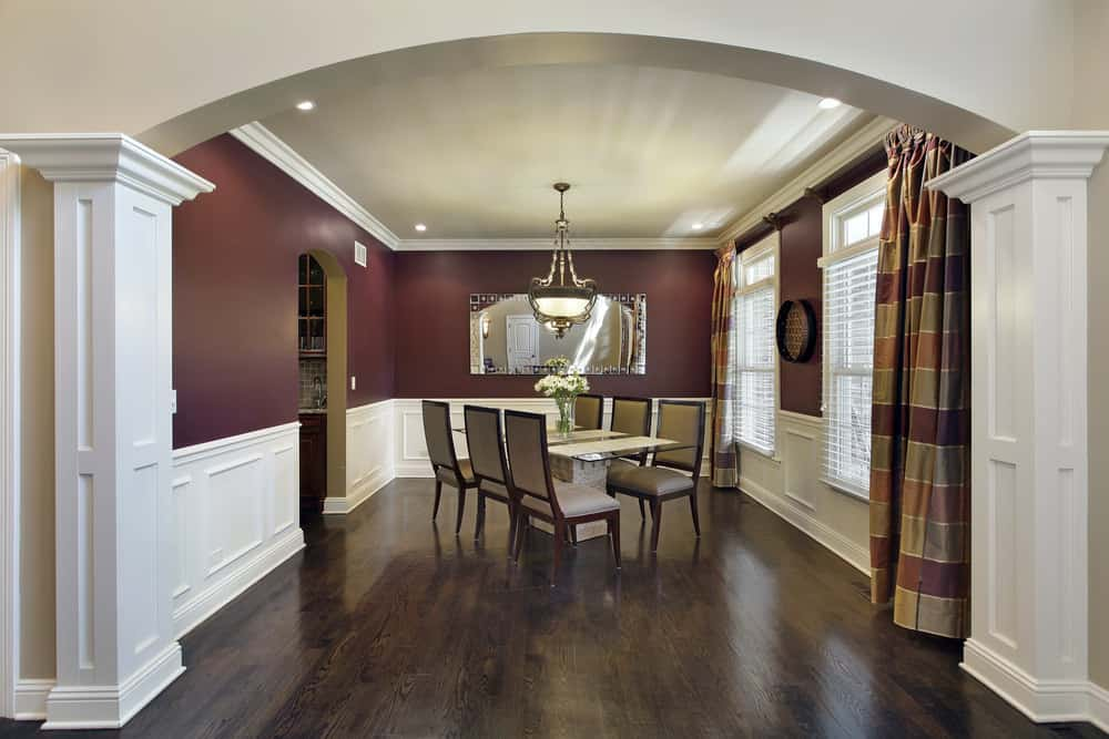 Burgundy dining room showcases a glass top dining table and upholstered chairs in a slanted layout. It is decorated with a rectangular mirror and a round wall art mounted above the white wainscoting.