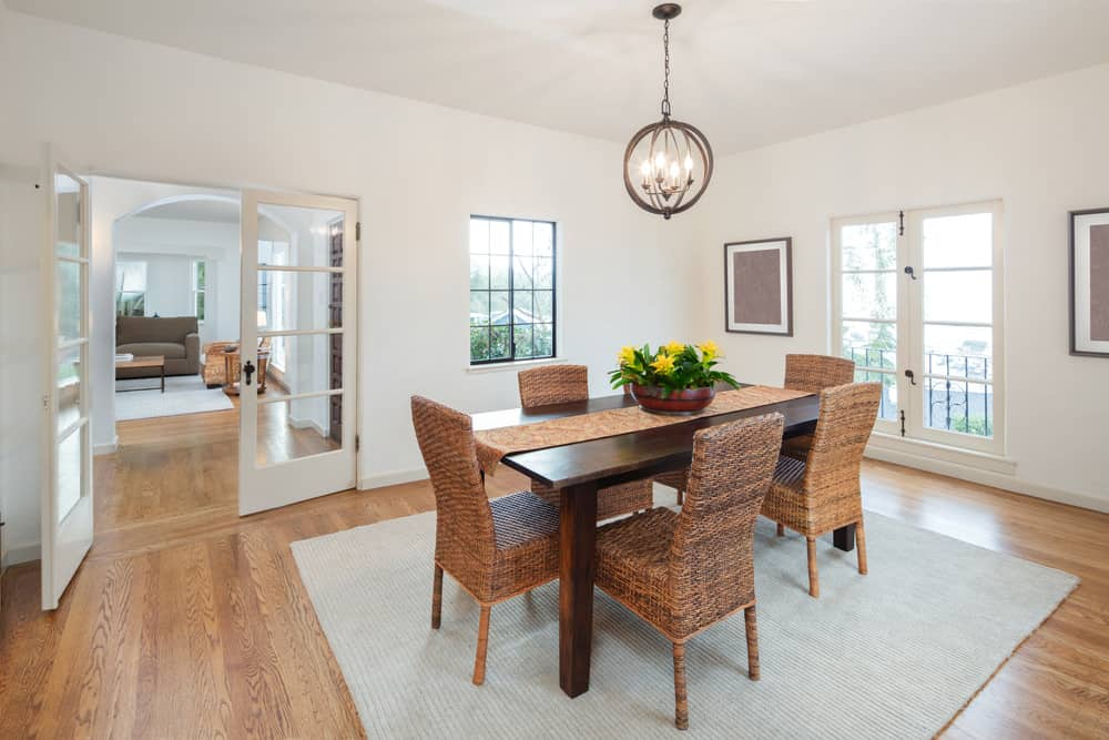 Wooden dining table with rattan chairs lighted by a round cage chandelier filled this white dining room.