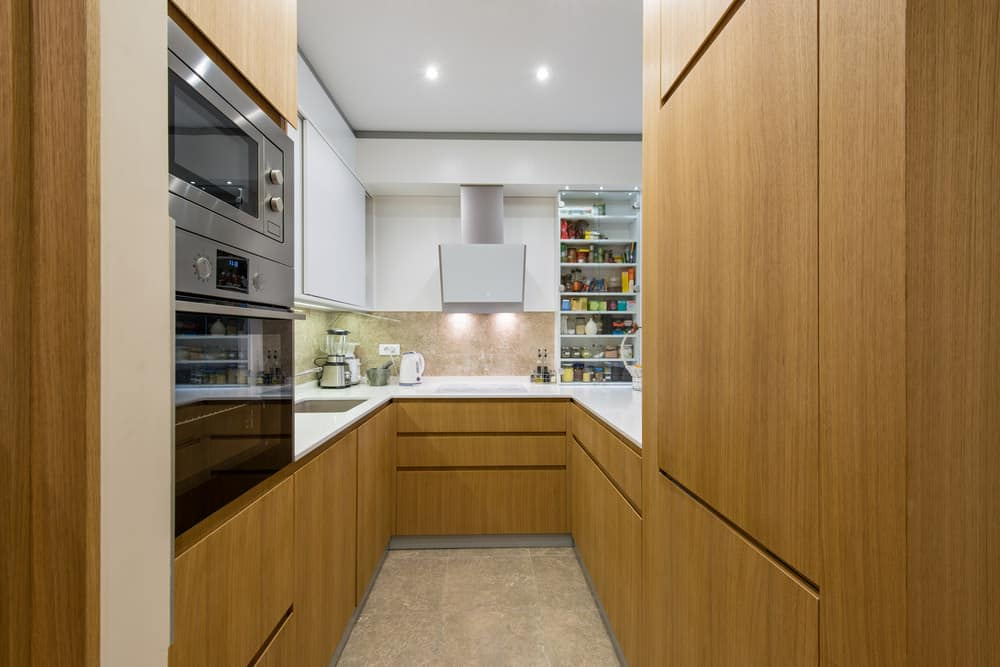 A narrow U-shaped kitchen with smooth white countertops and walnut finished cabinetry and counters.