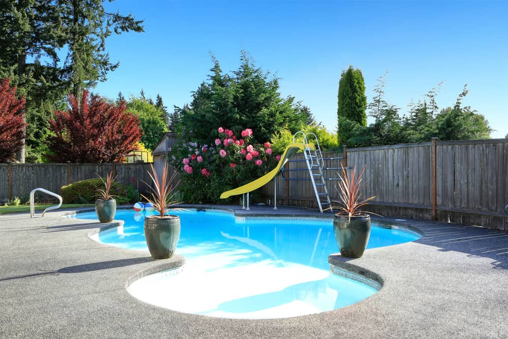 A stunning view of a custom free-form swimming pool with colorful flowers and potted plants around it.