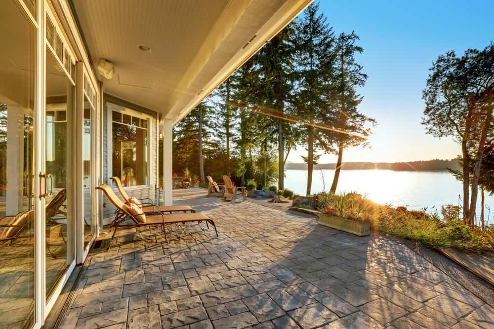 River-side patio area featuring lounger seats overlooking the beautiful nature.