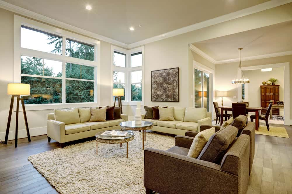 Large living room with cozy couches and classy rug and lighting.