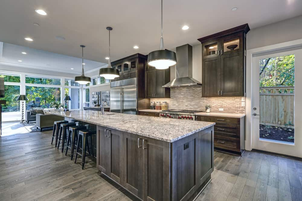 A modish large kitchen with a long center island featuring a marble countertop. There's a breakfast bar too, lighted by pendant lights. The kitchen also features a hardwood flooring.