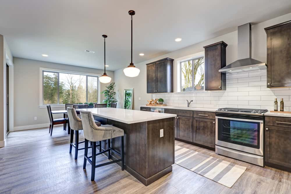 Large single wall kitchen boasting rustic cabinetry and kitchen counters featuring white countertops. The pendant lights brighten the center island with space for a breakfast bar set on the hardwood flooring.