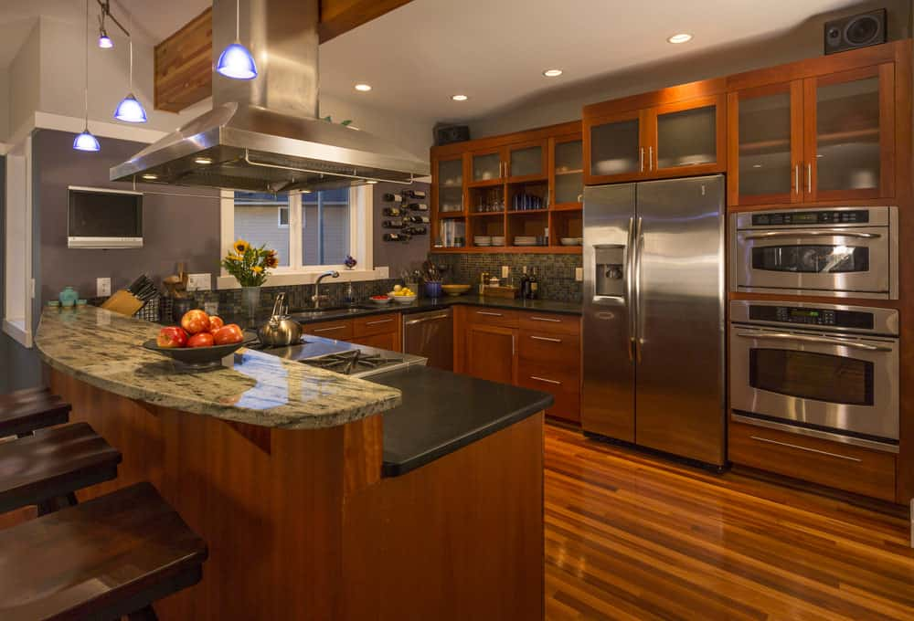 Rustic kitchen with a hardwood flooring matching the cabinetry and counters with black countertops. The breakfast bar features a marble countertop.