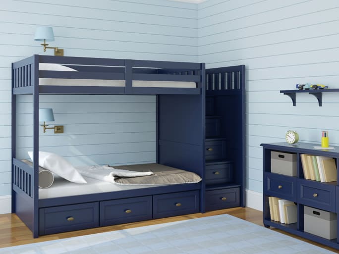 This boys bed features a bunk bed finished in navy blue paint, pairing up with the side table and shelving.