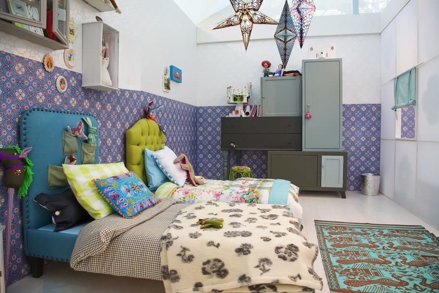A very stylish girl's bedroom with very attractive walls and ceiling decors, along with a couple of cute bed and a rug.