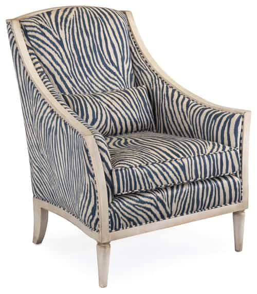 Weathered wood armchair with tall back and oversize cushions that feature blue and ivory zebra pattern.