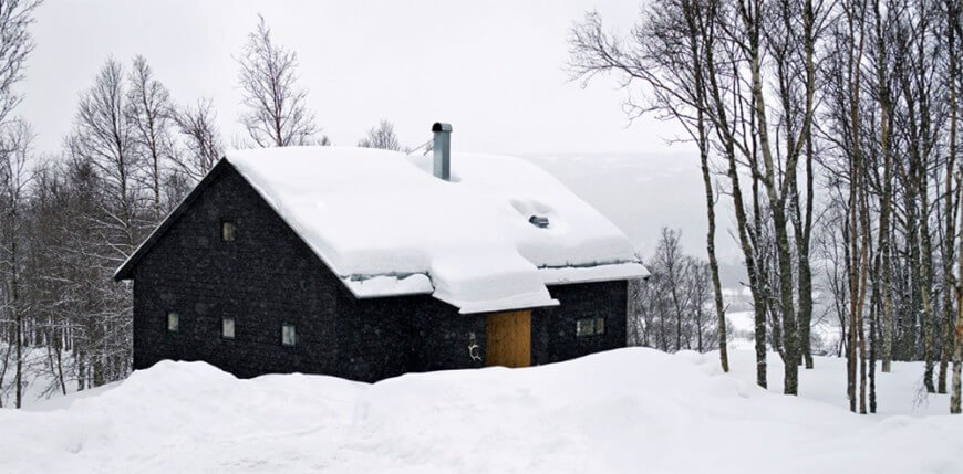 This is a close look at the exterior of this mountain home that has textured dark exterior walls that are almost black in contrast with the surrounding snowy landscape and tall trees. These also contrast the wooden main door.