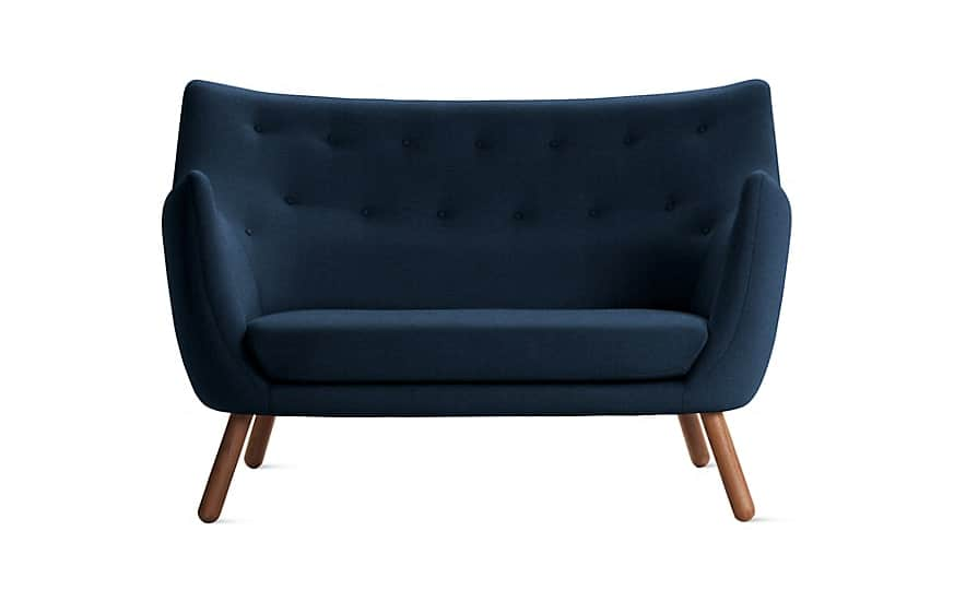 Sofa made of blue fabric upholstery with walnut legs.