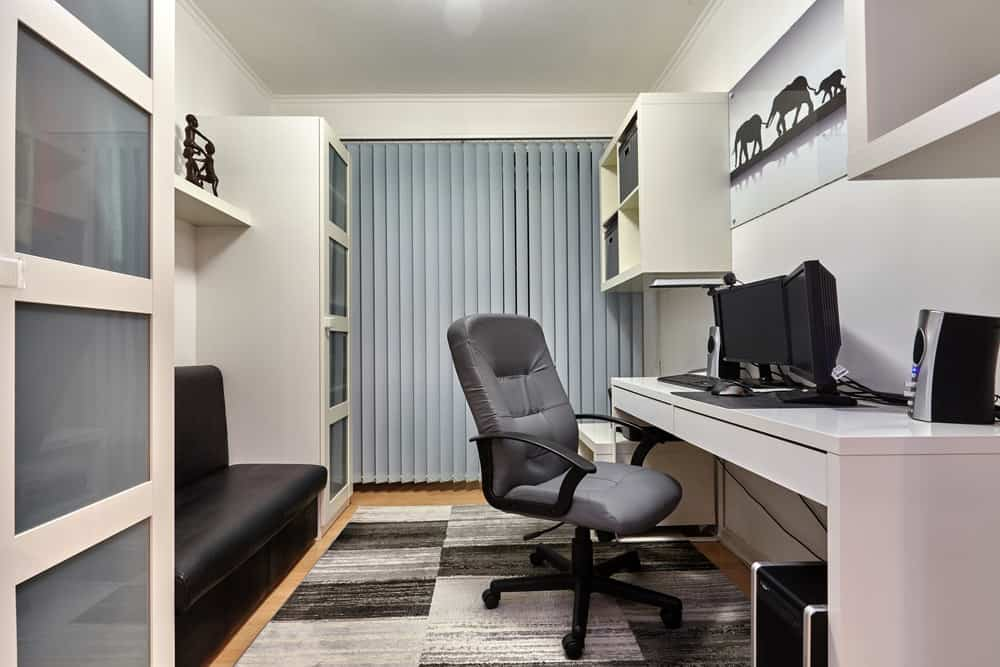 Home office with built-in shelving, rug and hardwood flooring.