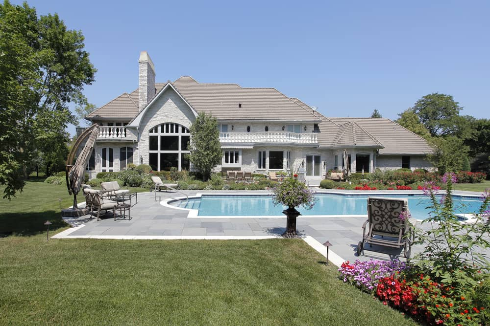 A view of a large free-form outdoor pool in an elegant dwelling surrounded by well-maintained lawns and colorful flowers.