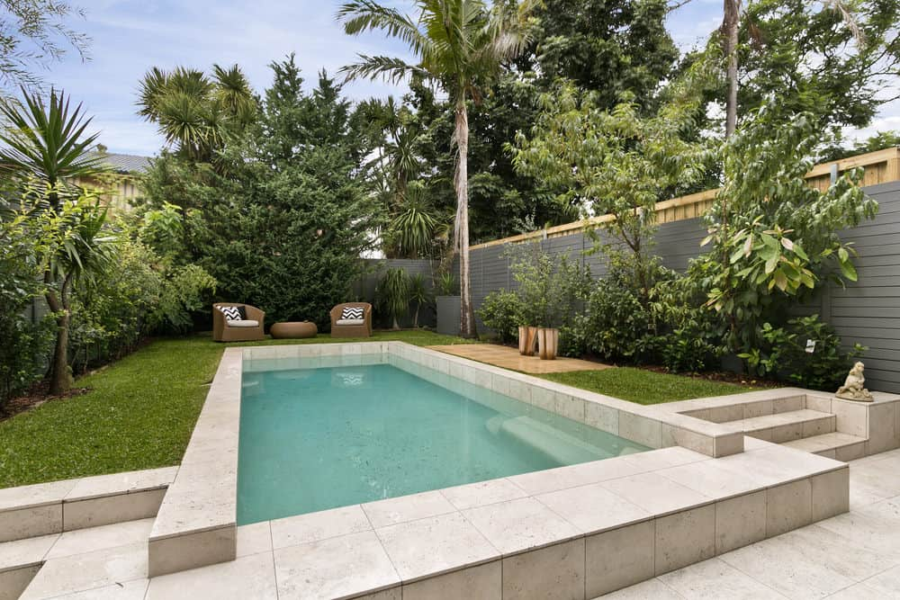 A rectangle outdoor pool surrounded by gardens.