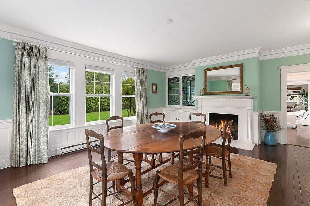 Mint green dining room features hardwood flooring and picture windows covered with patterned draperies. It has a wooden dining set and fireplace blending with the white wainscoting.