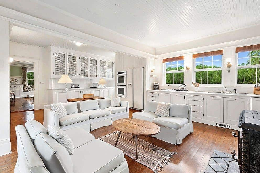 This great room features comfy seats on top of the hardwood flooring and under the white tray ceiling.