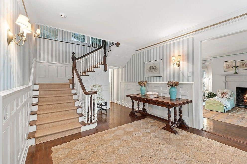 This farmhouse foyer has a hardwood flooring topped by a classy rug. The staircase looks very beautiful together with the elegant-looking walls and wall lighting.