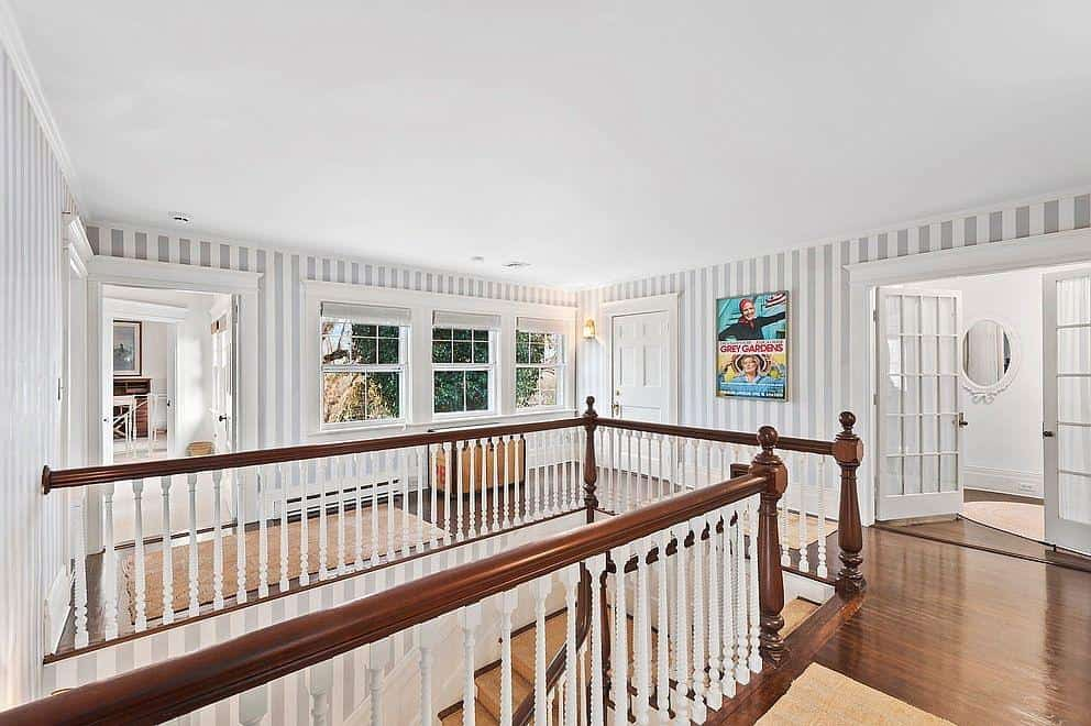This home boasts a second floor landing with stylish walls and hardwood flooring.