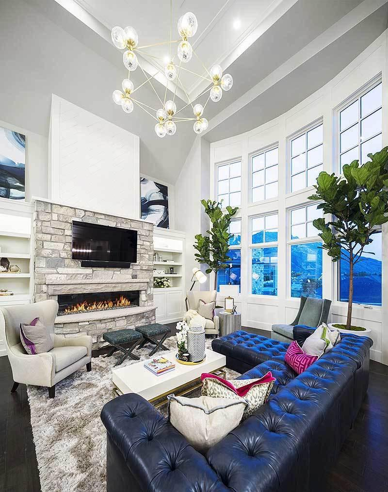 Large elegant living room featuring a classy chandelier, living room furniture sets and a fireplace with TV. The rug looks perfect with the room's style.