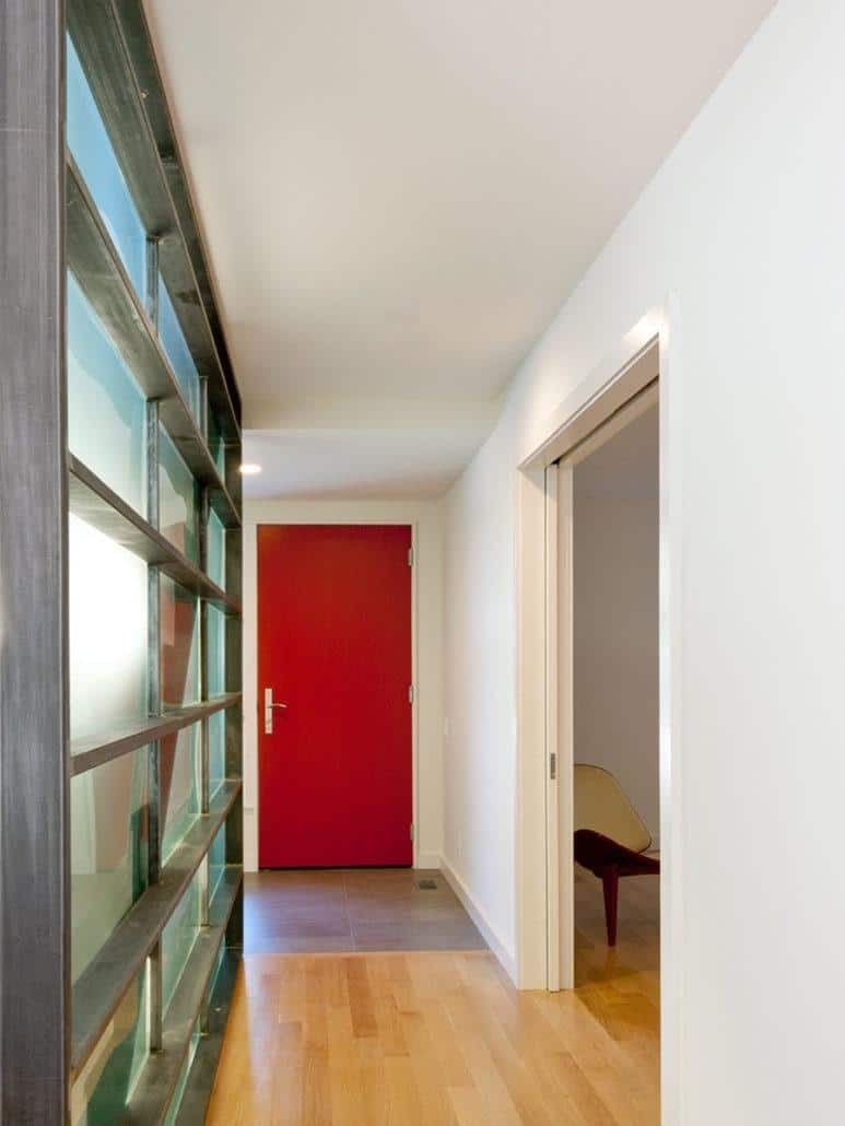 Narrow entryway features a vibrant red door against the white walls and hardwood flooring. There's a framed frosted glass window to its left.