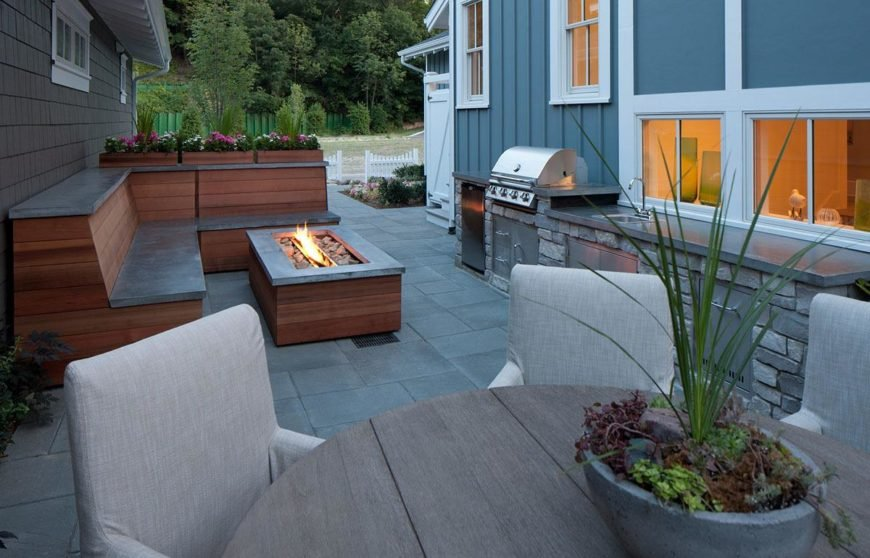 This patio area features a stylish bench seating and a fire pit near the outdoor kitchen and dining table set.