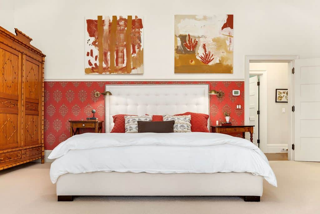 A well-organized primary bedroom designed with abstract artworks and a pristine white wall half covered in red patterned wallpaper that sets a striking backdrop to the tufted bed. It is complemented by a beautiful, custom wardrobe over beige carpet flooring.