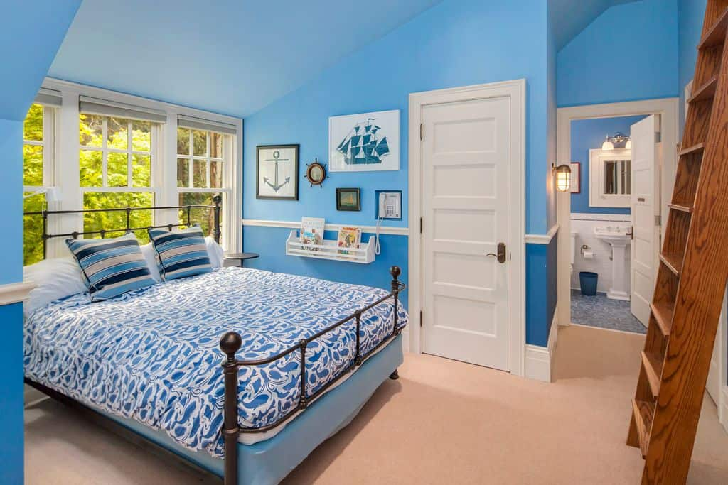 This boy's bedroom features sea-inspired walls and designs. The carpet flooring looks perfect for this room.