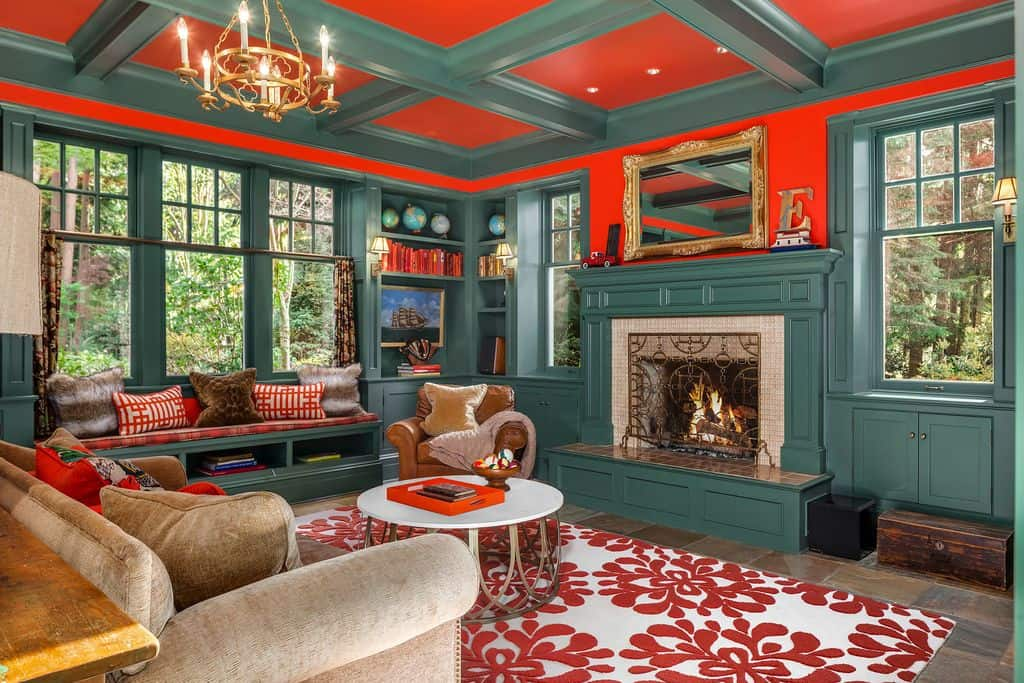 Farmhouse living room with red coffered ceiling and limestone flooring topped by a lovely floral rug. It has a gold chandelier and mirror that hung above the fireplace wrapped in an ornate fence.