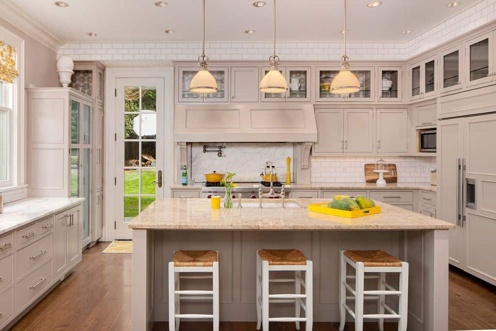 This kitchen features a large center island with marble countertops and hardwood flooring lighted by a nice set of pendant lights.