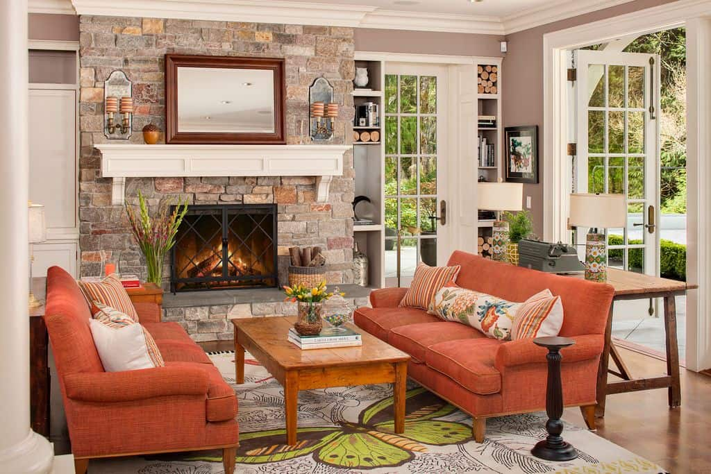 Farmhouse living room accented with orange sectionals facing each other with a wooden coffee table in the middle that sits on a butterfly printed rug. It has a fireplace enclosed in black metal that's fixed on the stone brick pillar lined with a white mantel.