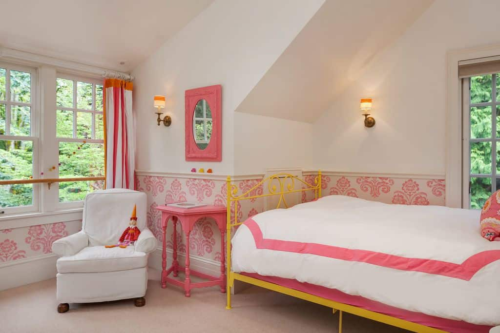 This girl's bedroom features nice walls with pink accent, lighted by classy wall lights.