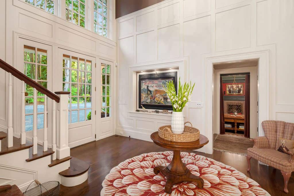 Farmhouse foyer boasting beautiful walls and a classy rug. The high ceiling looks towering and is very classy.