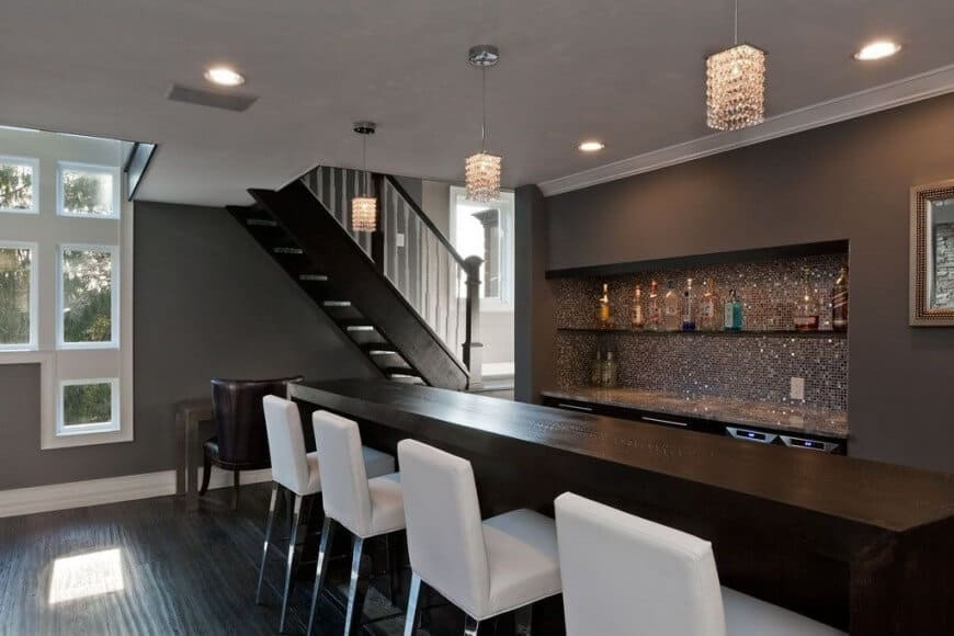 A modish bar set up on top of the hardwood flooring. It also features white bar stools and charming pendant lights.