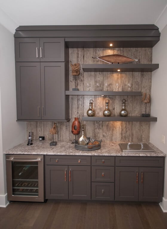 Rustic home bar with built-in shelving and cabinet together with marble counter and hardwood flooring.