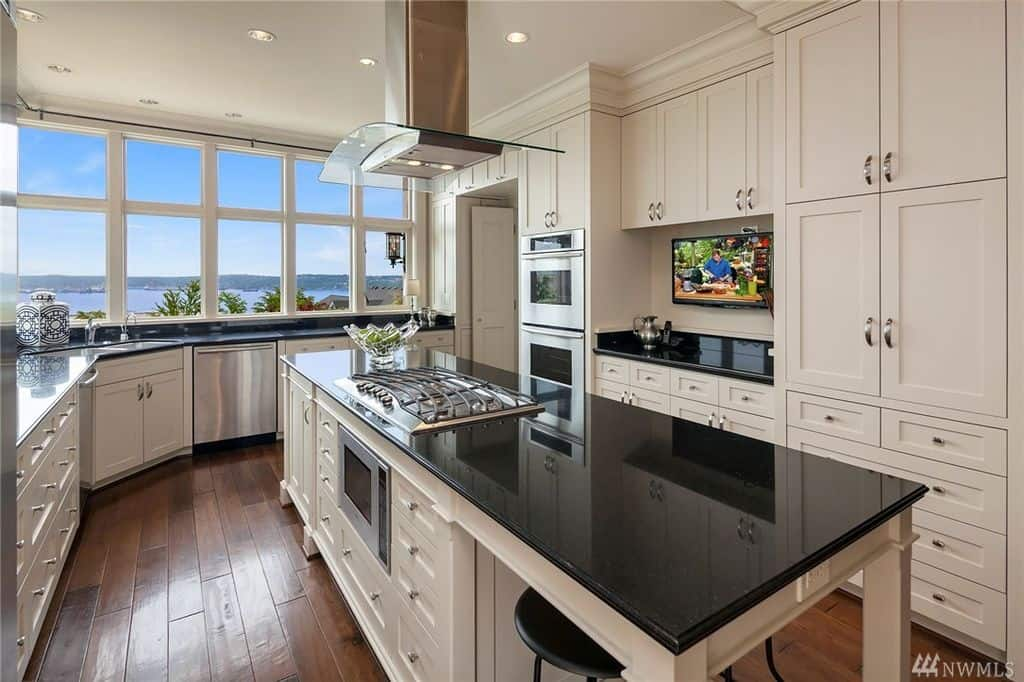 Stunning white kitchen featuring glass windows with a spectacular view, white cabinetry, stainless steel appliances and a large breakfast island with black granite countertop.